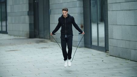 Sportsman training jump exercise on skipping rope. Athletic man jumping with skipping rope on street workout. Male athlete getting cardio training with jump rope in slow motion. Reklamní fotografie