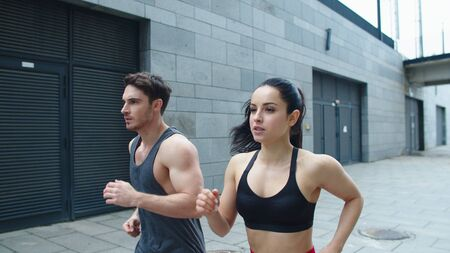 Closeup sporty couple starting run outdoor. Athlete man and woman training run exercise on urban street. Focused couple running together in slow motion. Reklamní fotografie