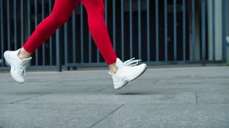 Close up female runner legs jogging on urban street. Closeup sporty woman training run outdoor. Side view of fitness woman running outside. Fit girl running in slow motion