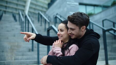 Portrait of smiling couple hugging outdoor. Cheerful man pointing finger to side. Excited man and woman standing on stairs together. Happy man embracing young woman at city street.