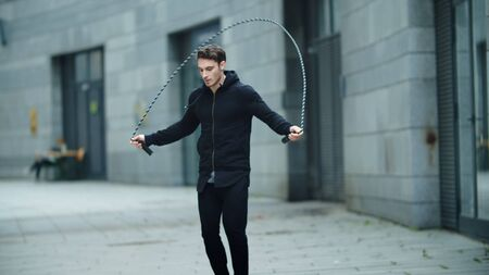 Fit man training jump exercise on skipping rope on street workout. Male athlete training with jumping rope outdoor in slow motion. Sporty man jumping on city street.