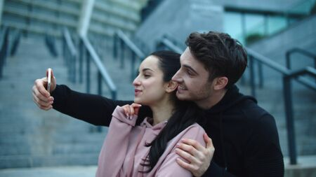 Hugging couple taking selfie on mobile phone. Smiling man and woman making mobile photo at city street. Couple in love posing for self portrait outdoor in slow motion Reklamní fotografie