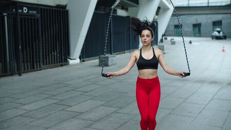 Athlete woman jumping on skipping rope on outdoor training. Fit girl doing jump exercise with skipping rope in slow motion. Sportswoman training cardio workout on city street. Reklamní fotografie