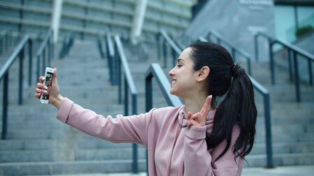 Happy woman making self portrait on smartphone outside. Portrait of fit girl taking photo slow motion. Close up sporty woman making selfie photo near stadium. Reklamní fotografie