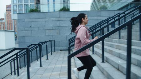 Athlete woman running up stairs on outdoor workout. Fitness girl jogging upstairs at city street in slow motion. Sport woman training run exercises on urban building background