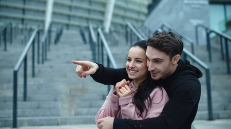 Laughing couple looking away in slow motion. Sporty man pointing finger. Happy man and woman embracing at city street together. Portrait of fitness couple having fun outdoor.