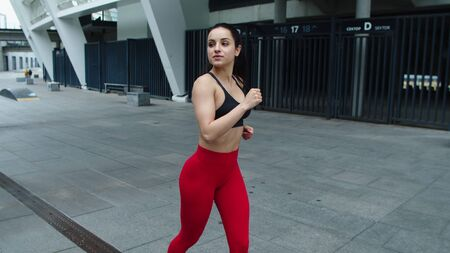 Attractive girl training run exercise on morning jog on city street. Young sportswoman running on urban street in slow motion. Sexy woman flirting on jog outdoor.