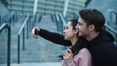 Fitness couple taking selfie photo to smartphone. Funny family posing for mobile photo in slow motion. Smiling man and woman having fun with smartphone. Sporty couple showing victory sign. Reklamní fotografie