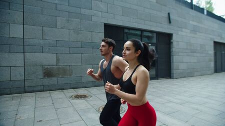 Sporty couple running outdoor together. Young man and woman training run on outdoor workout. Fitness couple jogging on urban street in slow motion. Sport couple running at city street
