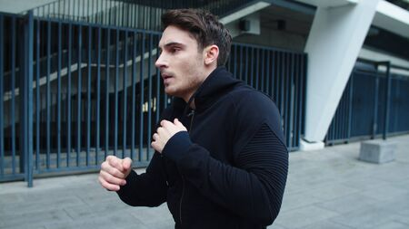 Portrait of young man training boxing punch on city street. Focused sportsman boxing outdoor in slow motion. Closeup handsome guy practicing beats on workout outdoor. Reklamní fotografie