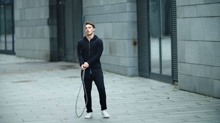 Fit man training on skipping rope on outdoor workout. Tired athlete training with jump rope in slow motion. Exhausted man finishing jump exercise with skipping rope on urban street. Reklamní fotografie