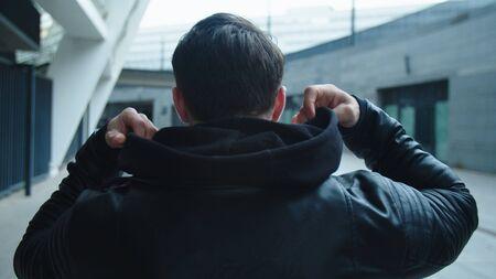 Lonely man walking on empty city street. Young man wearing hood outside. Back view of man walking away on urban street. Reklamní fotografie