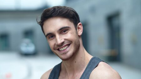 Close up smiling man looking camera outdoor. Portrait of cheerful guy smiling in slow motion. Sporty man posing on camera on city street.