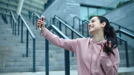 Close up smiling woman posing for selfie photo outdoor. Young girl touching hair in front of phone camera. Closeup happy woman showing victory sign for mobile picture. Reklamní fotografie