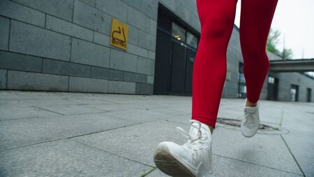 Woman legs running on street in slow motion. Close up female runner legs jogging on urban street. Sporty girl training run exercise outdoor. Closeup of fitness girl feet run in sport shoes