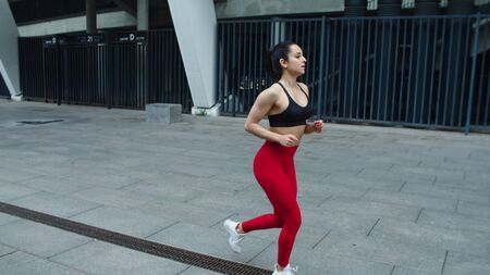 Sexy girl runner jogging near stadium in slow motion. Fitness woman training run exercise on urban street. Young woman running outdoors. Sport woman run workout outdoor