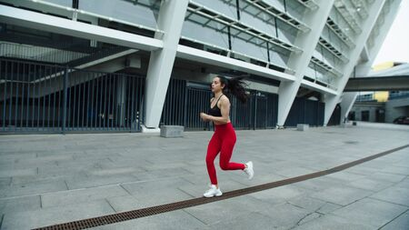 Beautiful woman running on morning training. Young woman jogging outdoor. Runner girl training run exercise on urban street in slow motion.