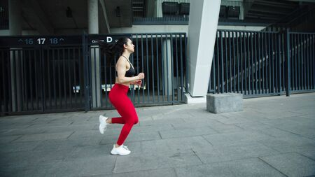 Fitness girl running outdoor in slow motion. Athlete woman training run exercise at street workout. Female runner jogging on city background Reklamní fotografie