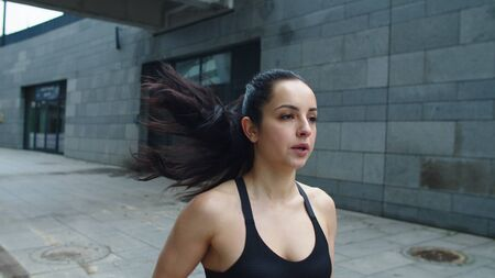 Close up cheerful woman running on urban street. Portrait of smiling woman training run exercise outdoor. Happy girl breathing on jog in slow motion. Reklamní fotografie