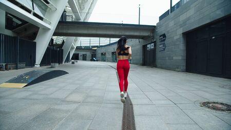 Athlete woman running outdoor in slow motion. Back view runner girl training run exercise on urban street. Sexy woman jogging on street background. Female runner running outdoor Reklamní fotografie