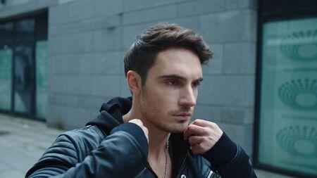 Portrait of young man walking street in black jacket. Handsome man correcting hood outside in slow motion. Closeup alone man going on urban street. Reklamní fotografie