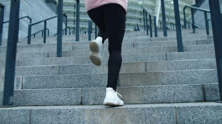 Closeup female legs running up stairs in slow motion. Close up fitness girl climbing upstairs. Back view of runner woman training run exercise outdoor.