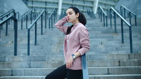 Fitness woman relaxing on staircase after workout outdoor. Young model posing on stairs in slow motion. Sporty woman standing in sportswear and smart clock on urban background.