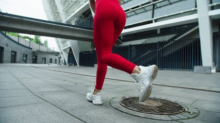 Closeup female legs running on urban street. Fitness woman training run exercise outdoor. Athlete girl jogging on city street in slow motion