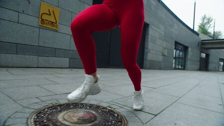 Closeup female legs running on urban street. Fitness woman finishing running in slow motion. Sporty girl jogging fast on city street. Fit girl training run exercise in city.