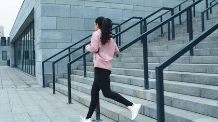 Fitness woman training run exercise on stairs. Sporty girl running down stairs in slow motion. Runner woman running on stairs at outdoor workout. Reklamní fotografie