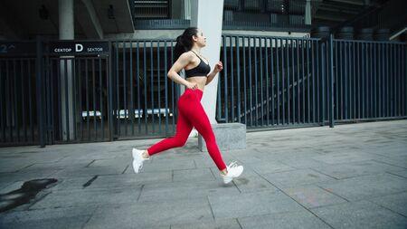 Female runner training outdoor in slow motion. Fitness woman running on urban street background. Sporty girl training run exercise on morning jog