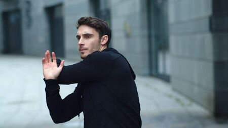 Handsome man stretching arms on workout outdoor. Close up fitness man training stretch exercise outdoor. Portrait of male athlete warming up before workout on urban street Reklamní fotografie
