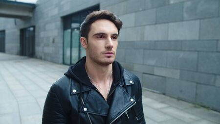 Closeup brutal man walking street in black leather jacket. Portrait of stylish man going on urban street in slow motion. Handsome man moving on gray wall background Reklamní fotografie
