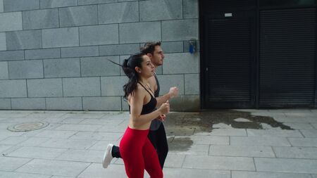 Sporty couple jogging at morning run. Fitness man and woman running at cardio training together. Young couple training run exercise outdoor in slow motion at city street. Reklamní fotografie