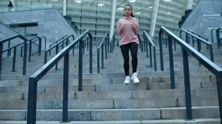 Sporty woman running down stairs on outdoor workout. Runner woman jogging down stairs in slow motion. Tired girl resting after stair running. Fitness girl breathing deep. Reklamní fotografie