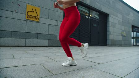 Fitness woman legs running on urban street in slow motion. Close up runner woman legs jogging outside. Sporty girl running outdoor in leggins. Fit girl feet run in sport shoes