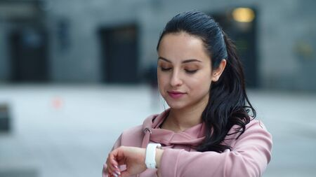 Close up pretty girl looking at fitness watch in slow motion. Portrait of focused woman setting mobile app on smart watch outdoor. Smiling girl getting funny message on mobile watch. Reklamní fotografie