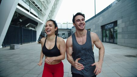 Close up cheerful couple running outdoor together. Laughing man and woman training run exercise on street workout. Happy couple jogging on urban street in slow motion.