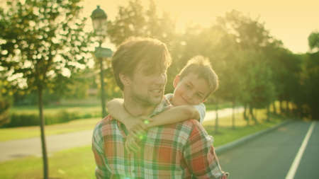 Smiling father giving son piggyback riding outdoors. Portrait of young man and boy talking together on street. Closeup happy father and son looking away. Happy family spending time together