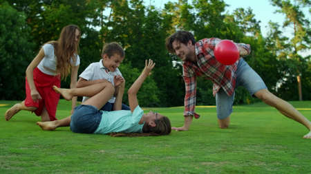 Smiling girl lying on grass with ball in field. Positive parents and son trying to get ball on green grass. Young family playing with ball in meadow. Joyful family spending time together outdoors