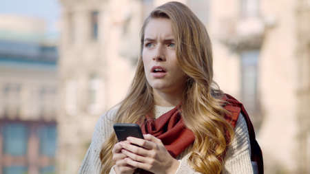 Portrait of upset hipster girl looking around in city background. Closeup stressed woman getting message with mobile phone outside. Disappointed girl checking notifications with smartphone on street. Zdjęcie Seryjne