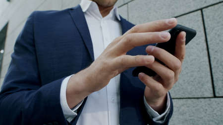 Close up businessman hands working on cellphone on urban street. Busy male employee browsing internet online on smartphone outdoors. Business man in formal wear typing on phone in slow motion Stock Photo