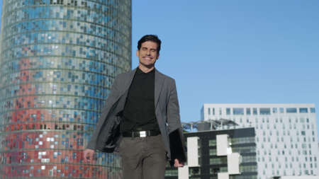 Joyful businessman walking on street with folder in slow motion. Excited business man turning around on urban street. Happy entrepreneur jumping in air outdoors. Cheerful worker enjoy success