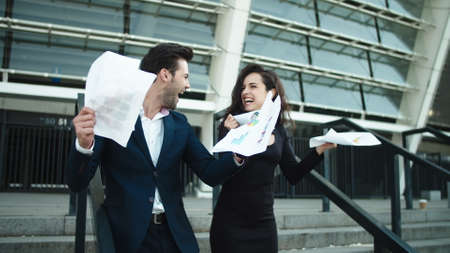Successful couple throwing papers in slow motion near stadium. Attractive couple celebrating victory together at street. Stylish business man and woman hugging together outdoors.