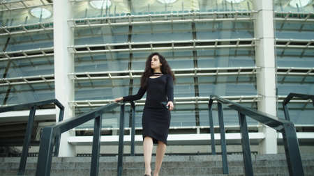 Attractive businesswoman entrepreneur walking downstairs in black dress outside. Sexy woman touching hair outdoors. Confident business woman looking away near stadium.