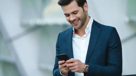 Portrait cheerful businessman using smartphone at modern street. Joyful business man smiling with phone in hand outdoors. Successful businessman talking phone in suit outside