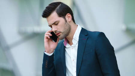Portrait confused businessman talking smartphone outdoors. Concentrated man having business phone talk at street. Serious businessman standing with phone in hand outside.