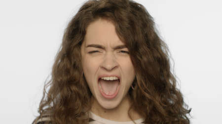 Angry woman screaming in studio. Portrait of rage girl scream on white background. Female person aggressive expression. Unhappy model angry. Close up of stress woman shouting