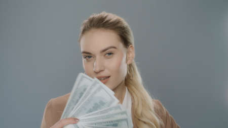 Young business woman holding cash money on grey background. Portrait of rich girl holding dollar money near face. Successful businesswoman fan with money cash in studio