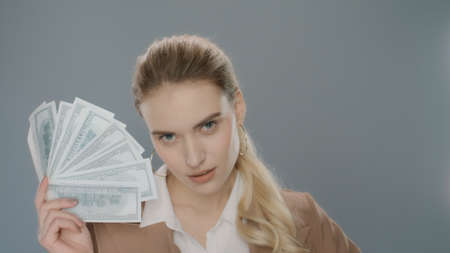 Sensual woman holding money fan on grey background. Portrait of young business woman showing money cash fan. Successful woman holding dollar money in studio. Businesswoman finance independence Archivio Fotografico